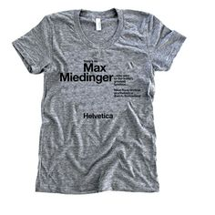 """Women's Helvetica T-shirt: The Women's Helvetica T-shirt is a tribute to a beautiful typeface and part of an ever-expanding typeface series from the husband-and-wife design team at The Social Dept. This gray T-shirt features black text that reads: """"Here's to Max Miedinger... who gave us the world's greatest typeface... Neue Haas Grotesk aka/Helvetica. Zurich, Switzerland... Helvetica"""" This is a shirt for the font-lovers out there; you know who you are."""