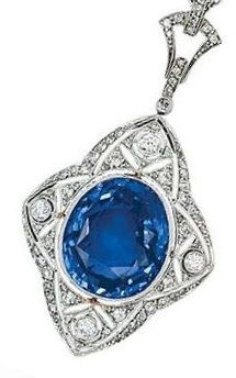 A Sapphire and Diamond Pendant Necklace, circa 1920.  The elongated quatrefoil motif set with an oval sapphire weighing approximately 15.25 carats, amid a diamond-set plaque finely millegrained and pierced with floral and foliate details, diamond-set bail, mounted in platinum.