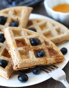 Easy Vegan Gluten Free Waffles on a white plate with fresh blueberries and syrup on top ready to be eaten, a fork sits on the side of the plate.