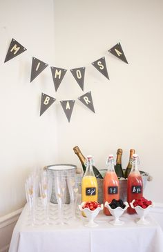 Mimosa bar for a bridal shower with fruit garnishes and gold detailed heart flutes!