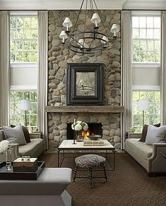 Living Room - Full stone wall fireplace with tall double windows adds to the traditional design bathed in a soft muted palette.