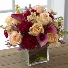 ftdC10-4857 Share My World Bouquet: Peach roses, peach stock, burgundy mini carnations, plum mini calla lilies, and accented with heather stems.  Ti leaves and red flax leaves line the inside of the vase $93.97