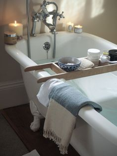 Plenty of candles and a wooden bath bridge packed with pampering essentials - the perfect bath time set up