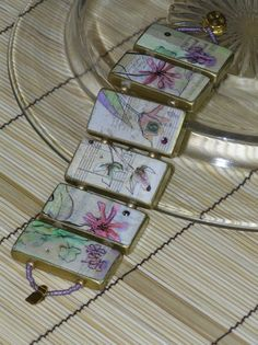 """Floral Tile Bracelet by KimberlysCraftini on Etsy. Did you know that you can drill through dominoes and make 'em into a bracelet? I DIDN'T!!! Then my husband bought himself a drill and I thought, """"Hmmm."""" This bracelet is made from 1"""" x 2"""" dominoes that have been decoupaged with decorative paper, aurora borealis micro glitter and crystal rhinestones. Each tile is rimmed in gold paint and varnished. They are connected with gold and lavender glass beads. I have two of these bracelets. $25.00"""