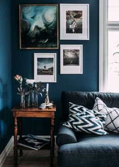 deep blue wall with gallery art wall and vintage wood table