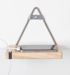 Tiagosen is a wall-mounted support piece for mobile phones that also holds your charger.