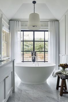 white bathroom with free standing tub, chandelier, white sheer draperies, Carrara Marble flooring.