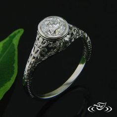 Custom 950 Platinum antique style mounting to hold a center bezel set 0.9ct round brilliant cut diamond. Engrave line detail around bezel. Pierced delicate scroll design on Side and top face of shoulders with hand engraved detailing.