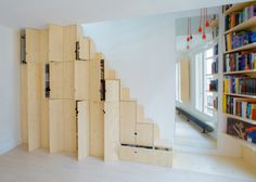 The staircase to the attic doubles as storage created by studio Schemaa