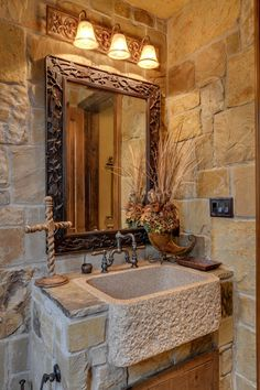 Unique powder room with stone walls, vanity.