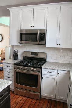 White shaker cabinets with Restoration Hardware Dakota pulls and knobs in Soft Iron.