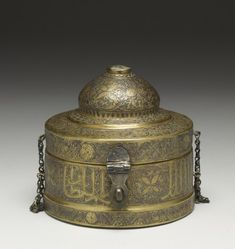 Persian (Artist)  PERIOD  14th century  MEDIUM  brass, silver, gold  (Metal)  ACCESSION NUMBER  54.516  MEASUREMENTS  H: 3 7/16 x Diam: 3 11/16 in. (8.8 x 9.4 cm)  GEOGRAPHIES  Fars, Iran (?) (Place of Origin)  This round box has a dome-shaped cover attached with chains on two sides, fastening in the front. Around the body is a broad band containing a thuluth inscription of blessings for the sultan. Persian verses decorate the cover along with arabesque patterns.