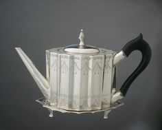 Teapot & Stand, c. 1796, Paul Revere II (1734-1818), Boston, Massachusetts – Revere's daybooks reveal that the silversmith made only nine teapots before the Revolution, & more than fifty teapots during the last two decades of the 18th century.  Unlike his earlier pear-shaped teapots that were raised from flat ingots, teapots of this fluted design were made from sheet silver that was formed around wooden patterns & then seamed.