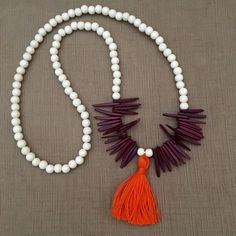 Perfect for Clemson Tiger fans, or just fans of bright pops of color, this handmade white beaded necklace with orange tassel and purple fringe is a great statement piece for your jewelry collection. M