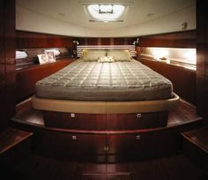 """Sea Ray 450 Sedan Bridge: The master stateroom's queen berth has a pillow-top innerspring mattress, 22"""" TV and twin cedar-lined hanging lockers. We like the cabinets over the hullside ports, and the shelves either side of the berth for keeping odds and ends at night. The master head is en suite."""