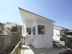 "The Corner House in Kitashirakawa / UME architects. A ""band"" attached to four sides on the second floor is used as a cabinet and a bay window that creates a space for planting, the display of objects, as well as a bench and a peak. This band reinterprets the traditional 'En'(veranda-like), 'Shoin'(study-like) and 'Toko'(alcove-like) 'Degoushi'(grilled oriel-like) and transforms an abundant residential configuration into expansiveness space.  photo © Yasushi Ichikawa"
