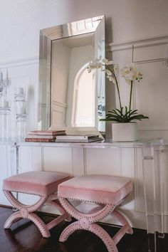 Elegant contemporary foyer is fitted fitted with pink velvet stools accented with a silver nailhead trim and positioned beneath a lucite console table topped with glass candle holders, stacked books, and a beveled mirror placed against gray wainscoting.
