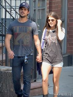 Taylor Lautner and Marie Avgeropoulos walk hand in hand through the streets of Soho in New York together. The new young couple stopped to take a selfy of themselves together before Taylor took a call while his lovely little lady waited patently by his side. July 29, 2013.