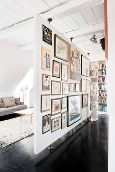 Room divider. Like the idea of lots of pictures. Could do bookcases with same effect.