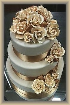 Gold Roses and Ribbons Adorn a 3-Tiered Silver Wedding Cake