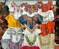 Display of blouses and several huipiles from Oaxaca and Chiapas at a market in the city of Oaxaca, Mexico