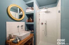 L'unico bagno, al piano inferiore, è suddiviso in due vani distinti. Nell'antibagno lavabo e box doccia sono disposti a 90°, divisi da un elemento strutturale che occupa la zona d'angolo. Le due funzioni sono identificate dalla piastrellatura in bianco, contrapposta all'azzurro carta da zucchero delle pareti.