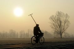 Abbiategrasso, Italy: A man rides a bike in the countryside by bethany