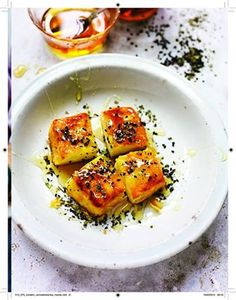 Halloumi Saganaki made by dusting halloumi in semolina before frying it in olive oil and drizzling with warm honey, black sesame seeds and oregano. Recipe from the TV series and book Rick Stein: From Venice To Istanbul.