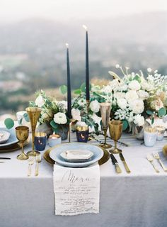 Elegant organic tablescape with a gorgeous green blue white floral candle centerpiece for an outdoor wedding