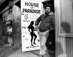 """My intention was to capture the grit and personality of a unique period in New York City history,"" Bobbe said in a statement about his series of images. Here, a man is pictured standing next to a cheeky sign on the streets of Times Square in the 70s."