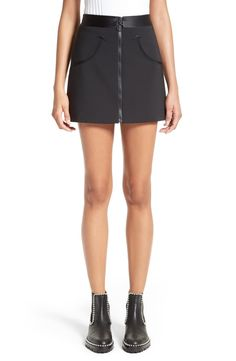 A matte black wetsuit zipper adds an athletic touch to this playfully short miniskirt finished with a lustrous silk waistband and artfully curved welt pockets for a dash of Western flair.