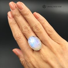 Check out this large beautiful flashy rainbow moonstone ring set in 925 sterling silver. This moonstone ring features a gorgeous quality oval cut rainbow moonstone cabochon with a clean modern setting and open back.  If you're looking for a rainbow moonstone statement ring, you've come to the right place. The striking rainbow flash of this ring will bring a little light to your day! Color your world with the chatoyant colors of orange, gold, cobalt blue and sky blue.