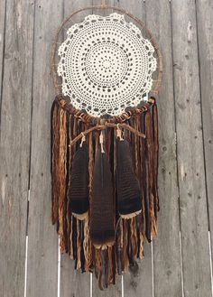 """Stardust' Dreamcatcher is a one-of-a-kind piece that will add a rustic, woodsy element to any room! Handmade with wood vine and sinew, this piece features a crocheted doily, cotton fabrics and lovely large wild turkey feathers. Measurements Total Length - approx. 3' Width - approx. 15"""""""