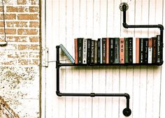 industrial decor - pipe bookshelf, in back section on the weatherboard wall above table. gloss black.
