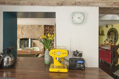 The teal tinted kitchen is accentuated with yellow appliances