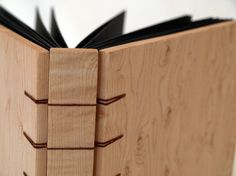 Solid wood book - you could bind the signatures on a thin wood spine that is slightly smaller than the visible spine and inlay it so the entire binding is hidden.