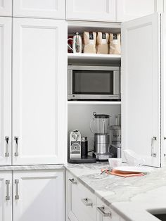 Counter Intelligence: A countertop cabinet provides a garage for everyday small appliances, another effort to maximize space and keep the petite kitchen free of clutter. Hope to make this happen in my next kitchen!