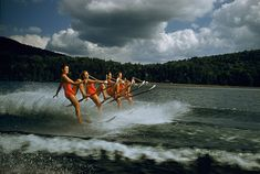 A women's water ski team lifts skis while being towed at 23 mph on Darts Lake in New York, 1956.Photograph by Robert Sisson, National Geographic Creative