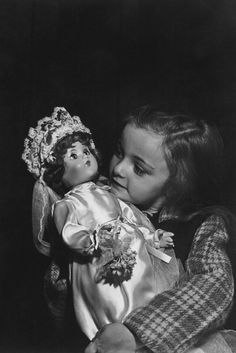 Beautiful vintage photo of a little girl holding a bride doll wearing a gown and veil.