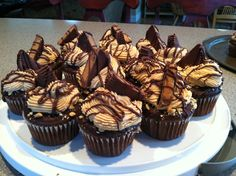 Reeses cupcakes! Chocolate peanutbutter cupcakes with a reeses egg center, dipped in chocolate ganache, sprinkled with crushed peanuts, topped with peanut butter buttercream icing, half a reeses cup, an drizzled with milk chocolate. Yum!