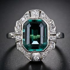 A bright electric teal green emerald-cut tourmaline is beautifully presented in platinum over gold, and almost half a carat of old-cut diamonds, in this stunning, colorful and far-from-ordinary cocktail ring of early twentieth-century vintage. A lovely scrolled gallery and hand engraving on the sides of the shoulders add the finishing touches.