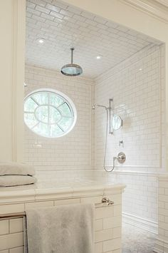 White subway tile walk in shower, no glass, circular window, tiled ceiling, rain showerhead, handheld showerhead....