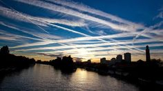Overdevelopment, Overpopulation, Overshoot - Airplane Contrails: Globalised transportation networks, especially commercial aviation, are a major contributor of air pollution and greenhouse gas emissions. Photo of contrails in the west London sky over the River Thames, London, England.