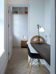 Working space in a corridor ~> clever use of space {white + fishbone wooden floor + Eames black chair}