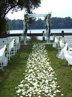 White Rose Petal Isle with Pew Flowers and a Decorated Arbor