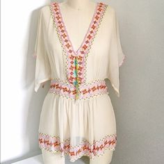 Antik Batik Sheer Silk Boho Top, Sz 40/Med Gorgeous silk, cream colored, sheer boho style top with red-orange, crimson, turquoise, green, lavender, and mustard embroidery. Also has a yellow, gold, and turquoise beaded tassel that can easily be taken off. Buttons up on the side for easy on/off. Ties behind the neck so it won't fall off the shoulder. Tag says size 40/M but I am an XS and can get away with this; just gives a more oversized look. Worn once for a photo. Accepting reasonable…