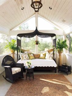 This outdoor space is so inviting with a covered wicker day-bed and a woven rug underfoot!  The neutral palette really lets nature pop! The perfect porch!