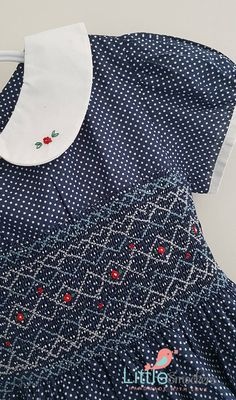 This beautiful blue polka dot girls dress has been made with a soft full cotton fabric with a hand smocked york adorned with hand embroidered red roses. The white peter pan collar has two embroidered roses and the sleeves have been finished off with white piping. Back closes with buttons and a looped tie back waist. Would suit a little girl who is between 6-7 years of age. Available in size 6 Chest measurement 24.5 around Length from back of neckline to hem 30