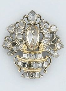 A George III diamond Giardinetto brooch. The floral spray set in the centre with a single oval rose-cut diamond within a table-cut diamond floral spray to a table-cut diamond set urn, in silver gilt mount, circa 1770.