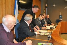 Zach Churchill, the minister of Municipal Affairs, is shown signing an agreement with the four Pictou County municipalities working toward regional government, watched by the mayors and wardens involved. The agreement provides more than $27 million over five years to help with the costs of amalgamation, if the merger is approved. CAROL DUNN – THE NEWS Atlantic Canada, Churchill, Regional, Affair, News